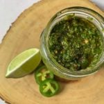 top down view of chimichurri sauce in a glass jar on a slice of wood