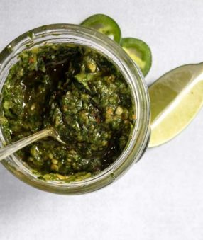 top down image of cilantro chimichurri sauce in a jar with spoon sticking out