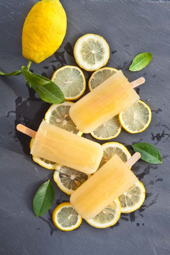 popsicles and lemon slices on a gray slate