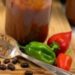 peppers, coffee beans, and bbq sauce on wood cutting board