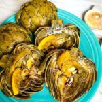 roasted artichoke halves on a turquoise plate