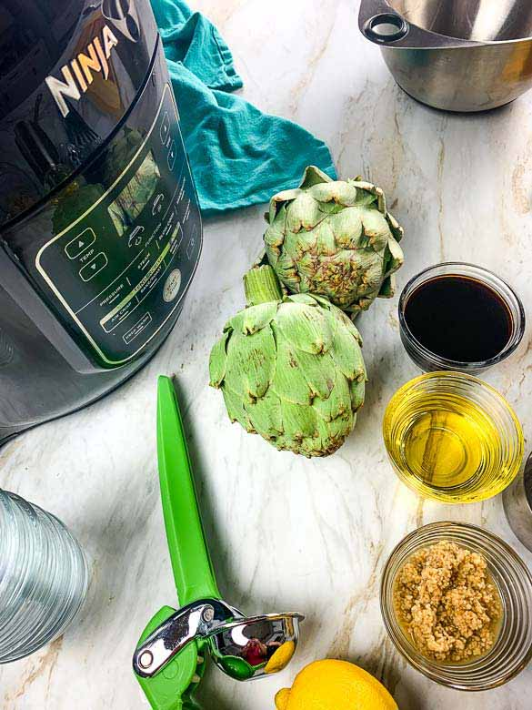 ninja foodi, artichokes, and other ingredients on white countertop