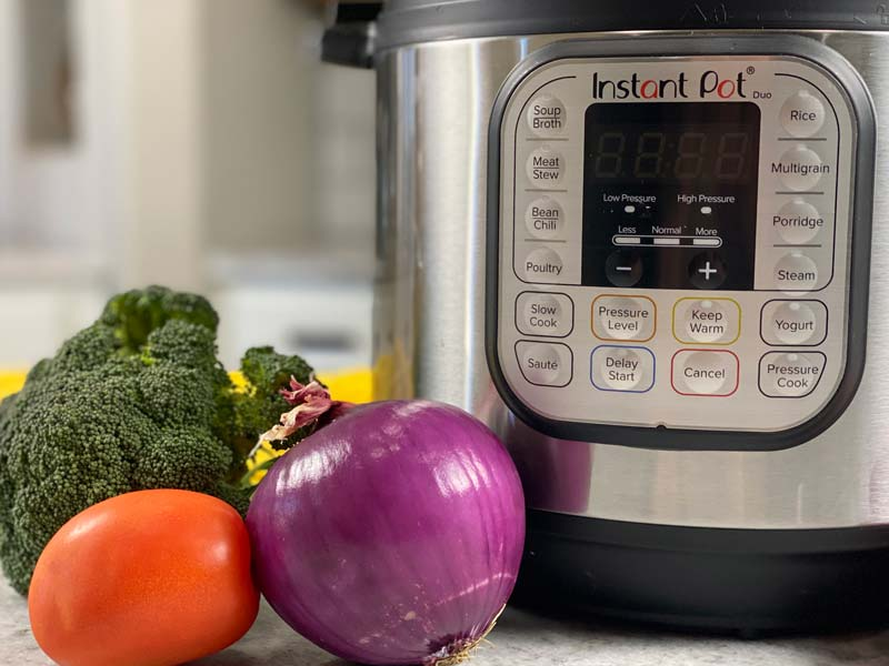 close up of instant pot with veggies off to the left