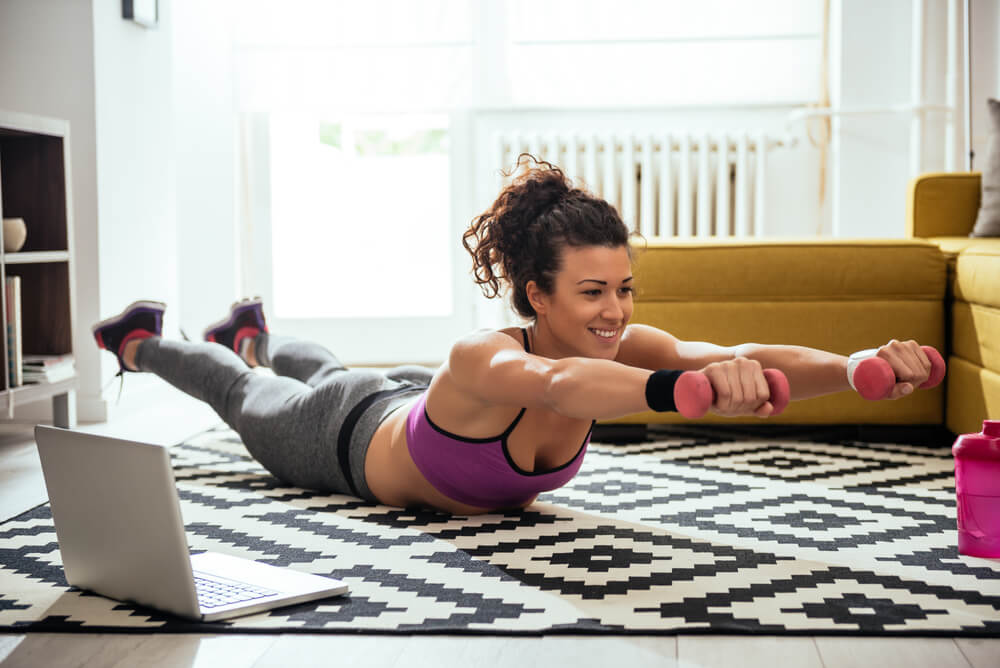Woman working out at home with weights.