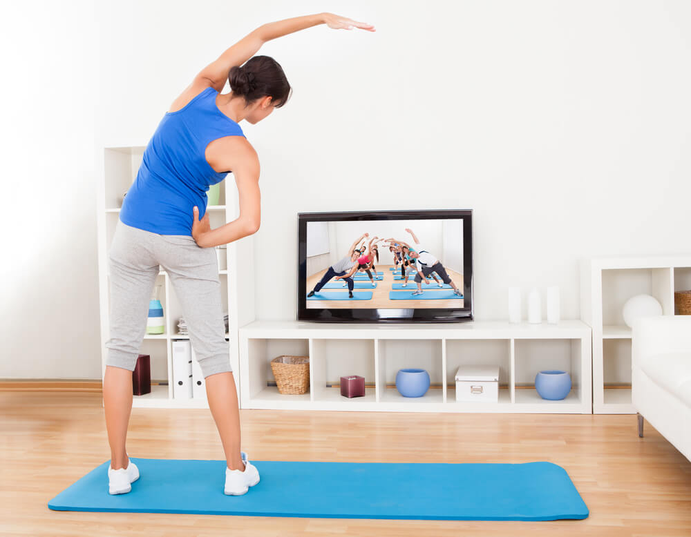 Woman watching workout on tv and exercising.