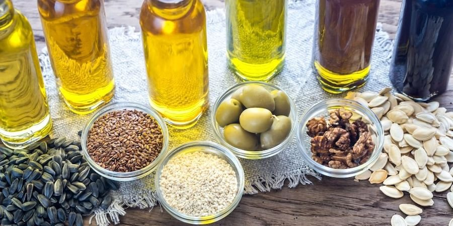 variety of oils in bottles in front of their main ingredients.