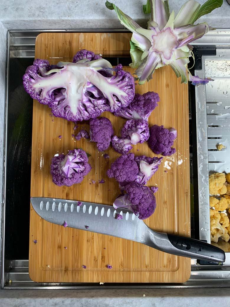 cut cauliflower on a wood cutting board