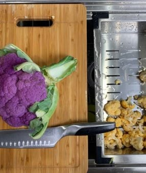purple cauliflower on wood cutting board