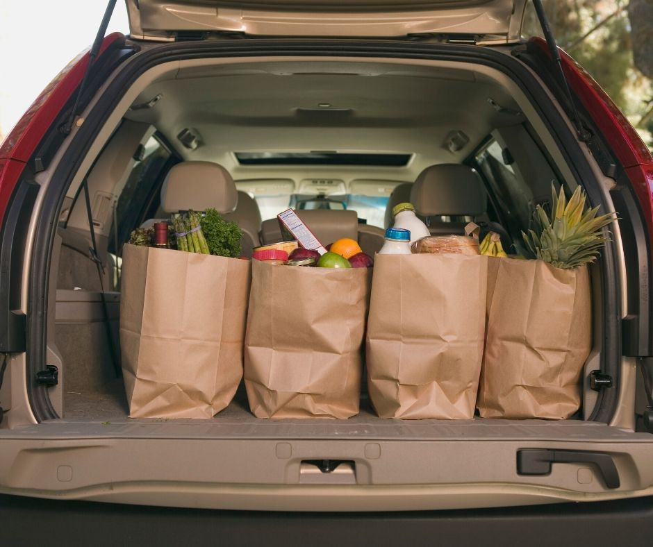 Groceries in bags in the back of the car.
