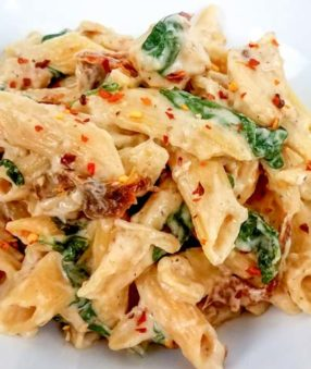 tuscan chicken pasta in a white bowl