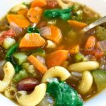 close up of minestrone soup in white bowl