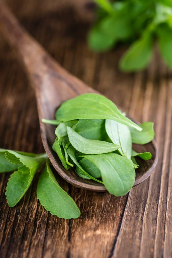 stevia leaves on a wooden spoon