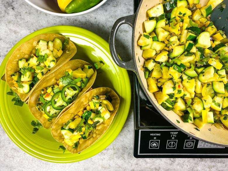 calabacitas in a pan and three calabacitas tacos on a green plate