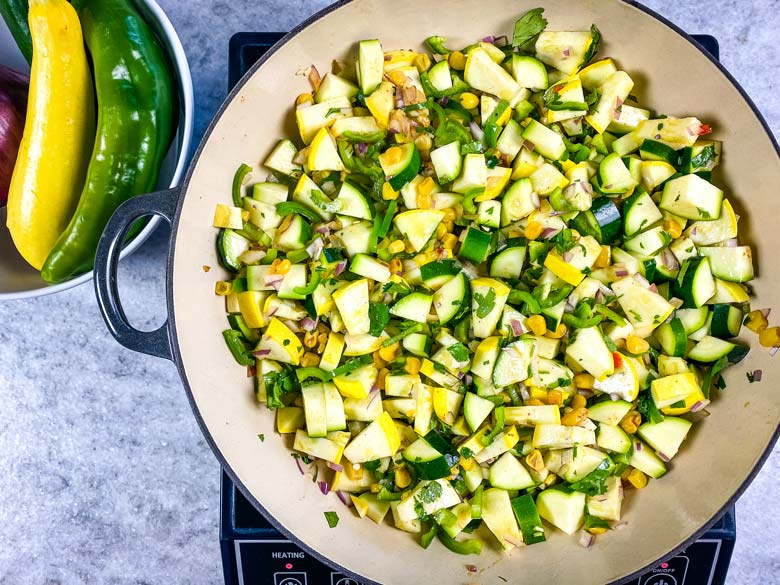 pan of calabacitas on a burner on the counter