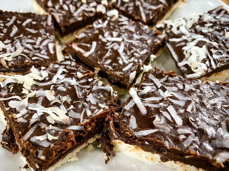 close up of coconut bars on white plate