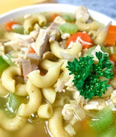 close up of turkey carcass soup in a white bowl