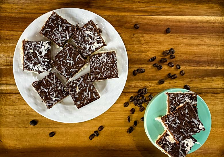 coconut bars on white plate with coffee beans