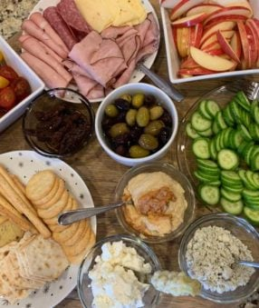 snacks and appetizers on a wood platter