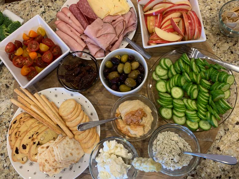 appetizers and snacks on a wood platter