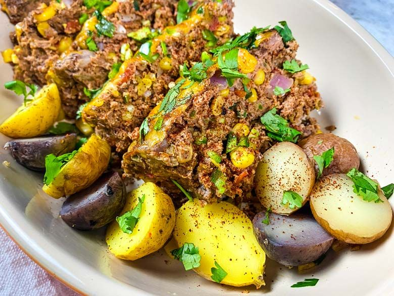 close up of sliced meatloaf with roasted potatoes