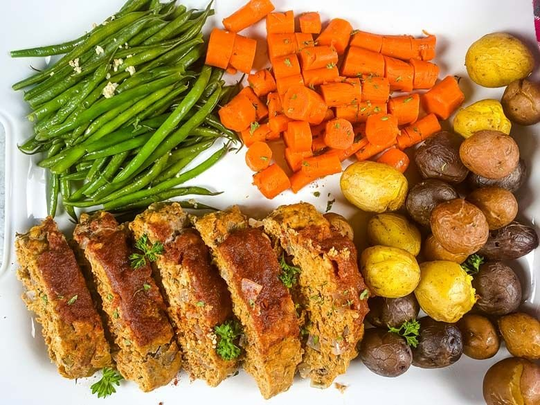 Overhead picture of cooked meatloaf, potatoes, carrots, and green beans.