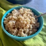 close up of brown rice in a blue bowl with spoon
