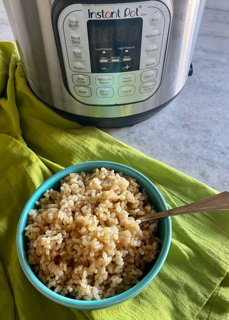 blue bowl of brown rice in front of an instant pot