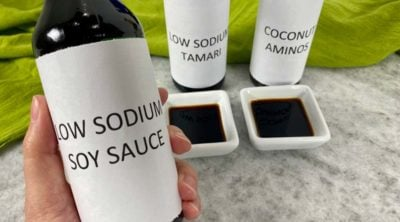 holding a bottle of low sodium soy sauce with aminos and tamari in the background