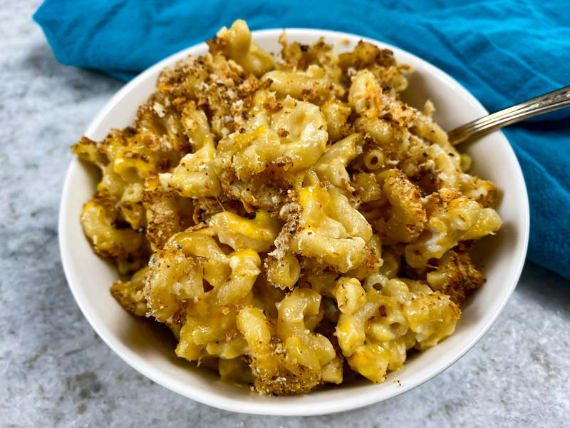close up of mac and cheese with breadcrumbs in white bowl