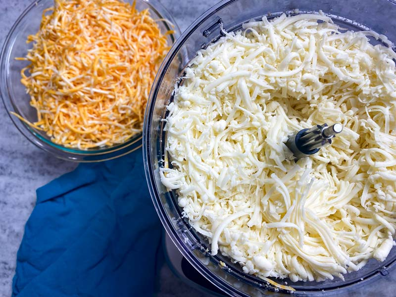 two types of shredded cheese in a food processor and glass bowl