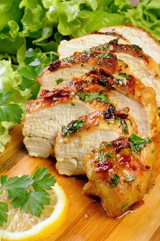grilled chicken on a wood cutting board with lemon and lettuce