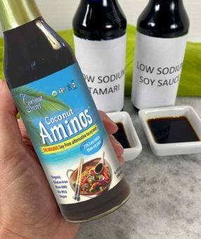 hand holding bottle of coconut aminos