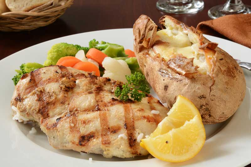 grilled chicken, vegetables, and a baked potato on a white plate