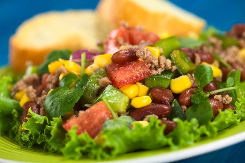 salad with ground beef on a white plate