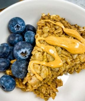 bowl of amish baked oatmeal with blueberries on the side and peanut butter on top