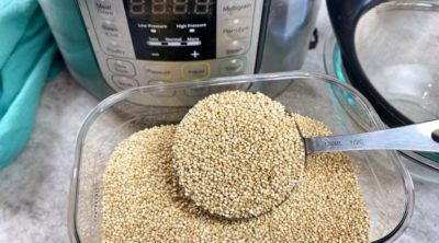 dry quinoa in a measuring cup in front of an Instant Pot