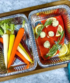 peeled carrots and grilled salmon in foil tins