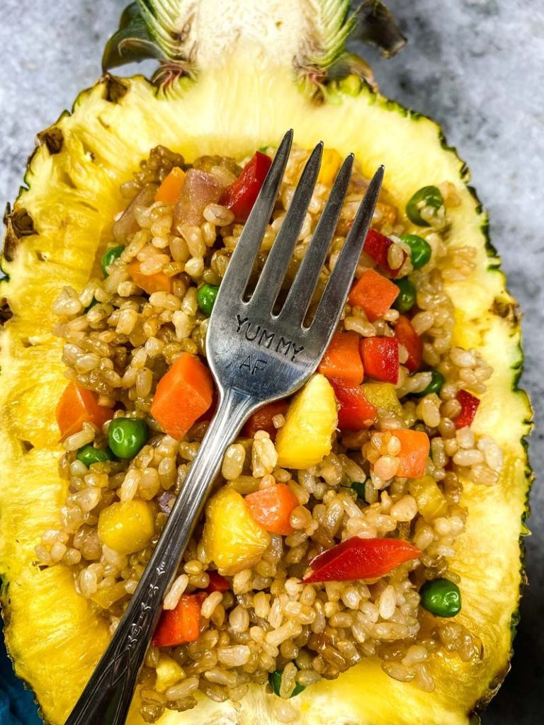 close up of half of a pineapple with pineapple fried rice inside