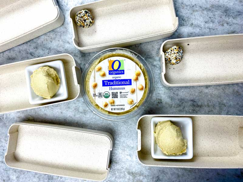 empty bento boxes filled with goat cheese and hummus