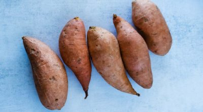 medium sized uncooked sweet potatoes on the counter