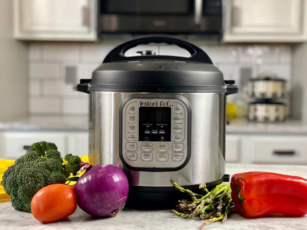 instant pot on counter with fresh vegetables next to it