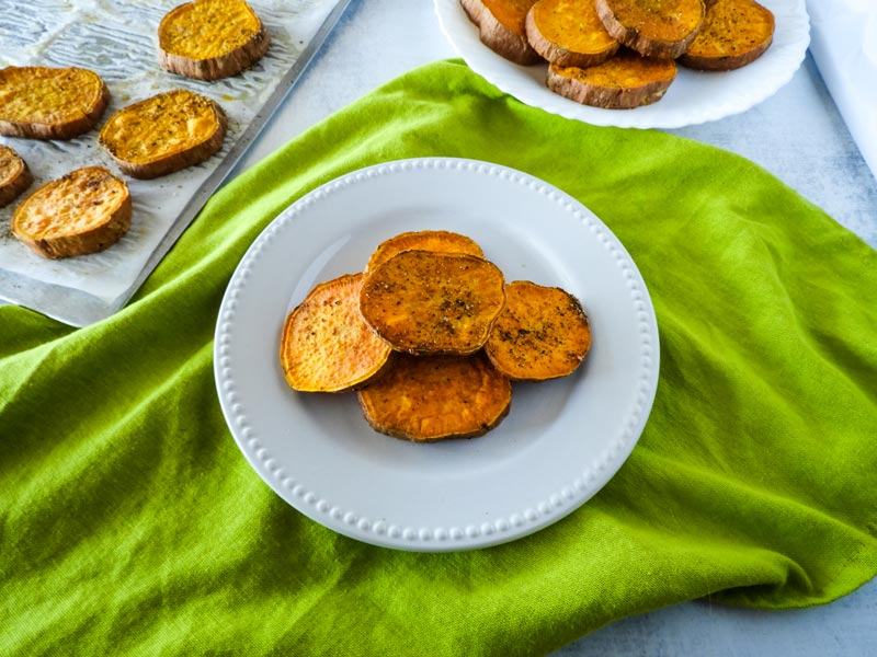 roasted sweet potatoes on a white plate with a green napkin