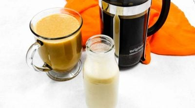 french press coffee with homemade creamer on a white counter
